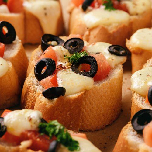 Тосты с моцареллой, помидорами и оливками